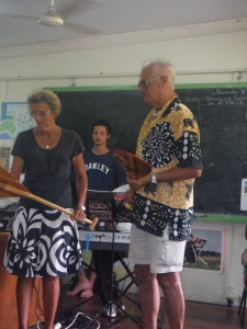 Derrick is showing the kids a sample of the 30+ paddles we brought to donate to their club.